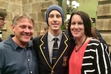 A student in a school blazer and beanie flanked by his parents.