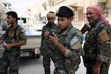 Four fighters from the Syrian Democratic Forces stand on a run-down street in Raqqa.