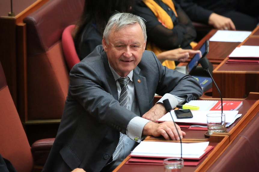 Gallacher seen in a grey suit leaning on his desk in the senate chamber.