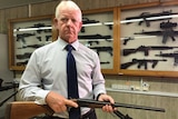 Peter McErlain has a stern look on his face as he holds a rifle and stands in front of a cabinet of guns.