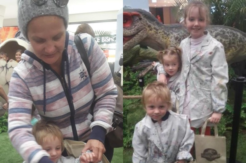 A woman holds the hands of a little boy and three children pose together in front of a dinosaur statue