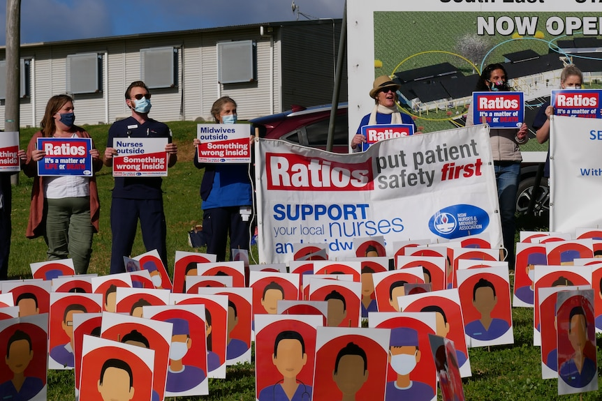 Signs with cartoon healthcare workers, and people standing behind.