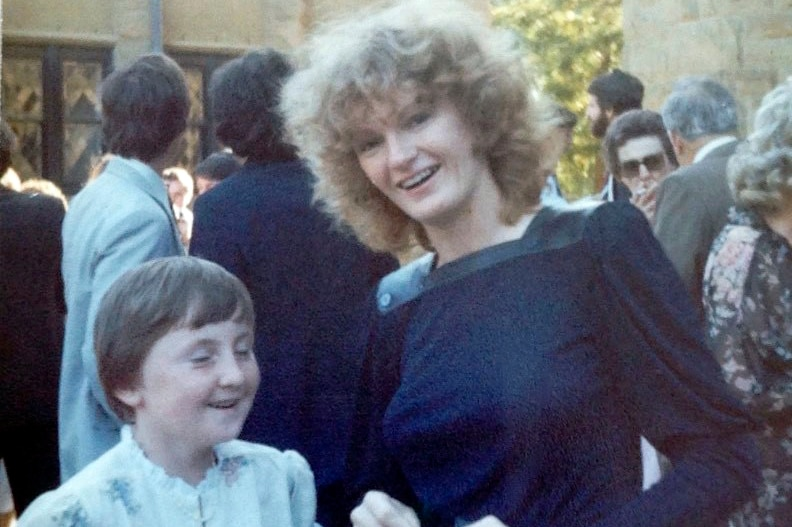 Rhonda Favaloro with curly blond hair wearing a navy dress.