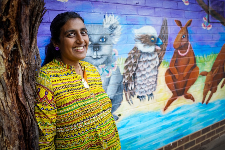 A woman in a yellow blouse poses for a portrait in front of a colourful wall