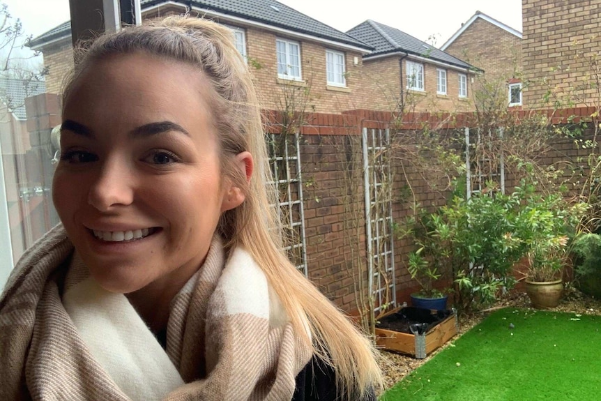 Grace Calvert smiles with a big winter scarf, she is in front of a window that looks out into a small yard at her home.
