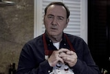Kevin Spacey, wearing a Christmas-themed apron, puts a ring onto his finger while starting at the camera.