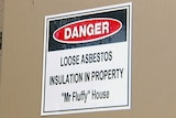 Sign on fuse box identifying a house as a Mr Fluffy loose-fill asbestos home.