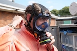 A man in a gas mask and hi-vis