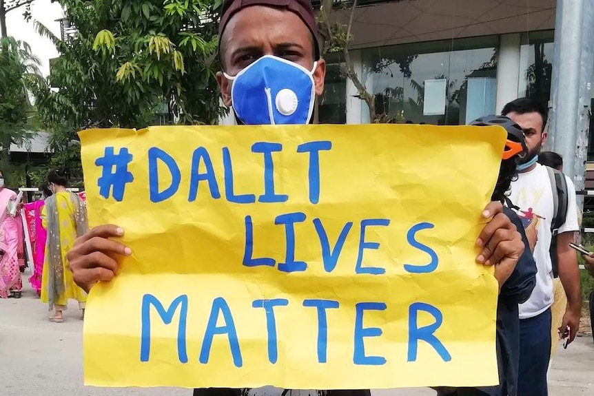 """A man wearing a facemask holds a sign saying """"# Dalit Lives Matter""""."""