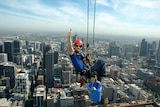 A man abseils from a building with a vista of Melbourne behind him.