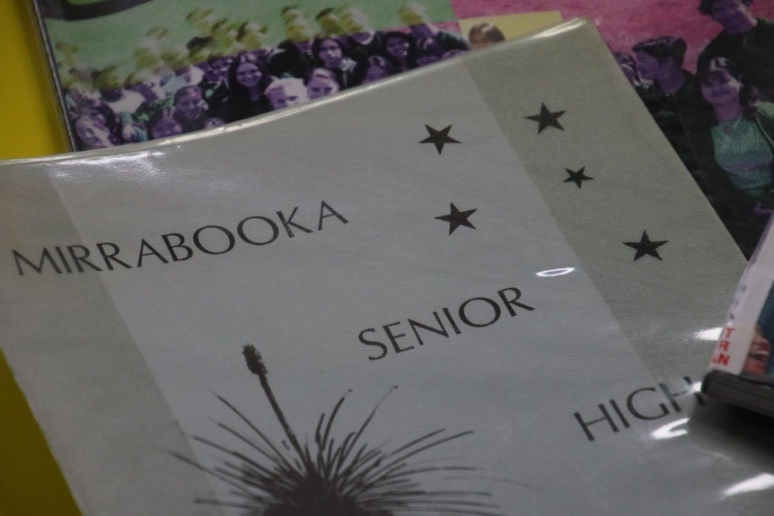 A close up of a grey school year book, that reads 'Mirrabooka Senior High', with stars and a cartoon grass tree on it.