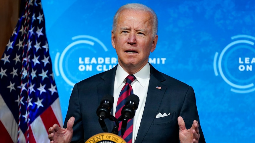 Joe Biden speaks behind a lectern with the US Presidential seal, in front of a blue digital screen.