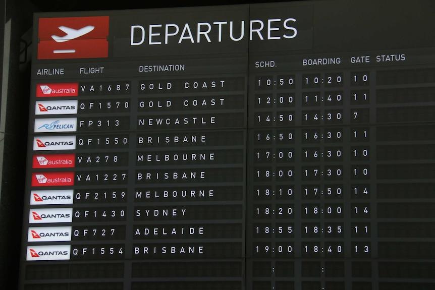 An airport screen shows flights to Queensland.