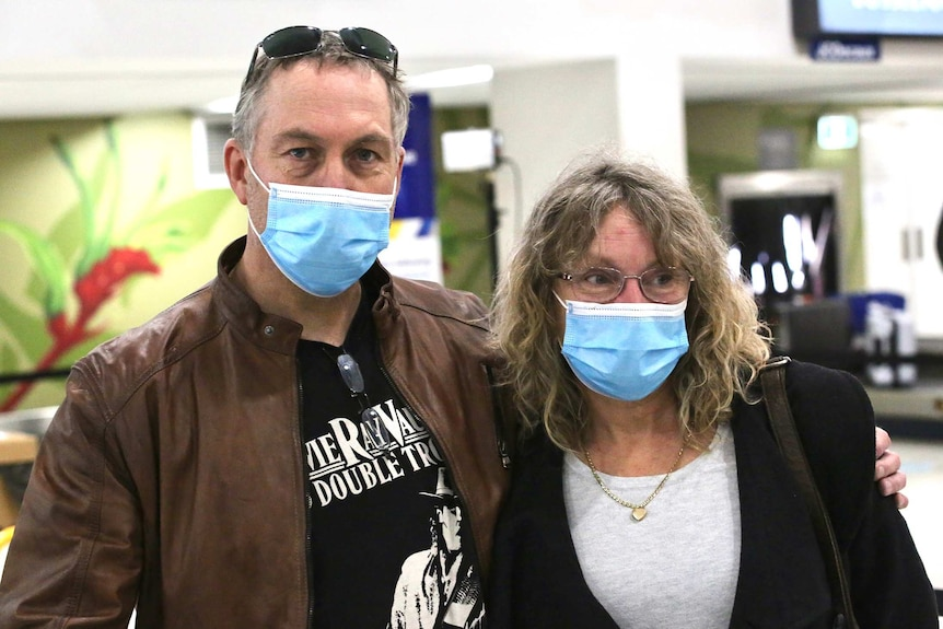 A man and a woman stand posing for a photo in an airport terminal wearing face masks, with the man's arm around the woman.