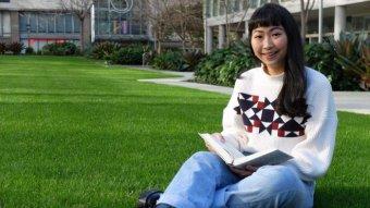 Shu Xian Leong holding Bible, sitting on grass.