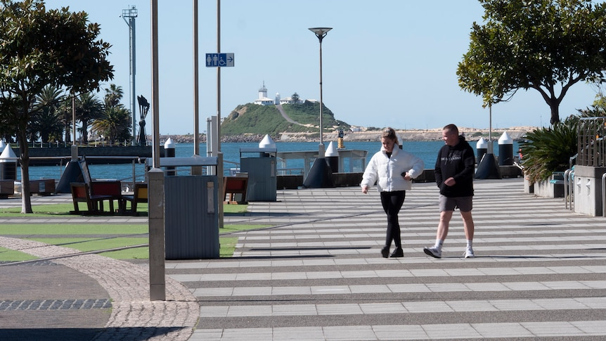 Two people walking along promenade in Newcastle with the ocean in the background