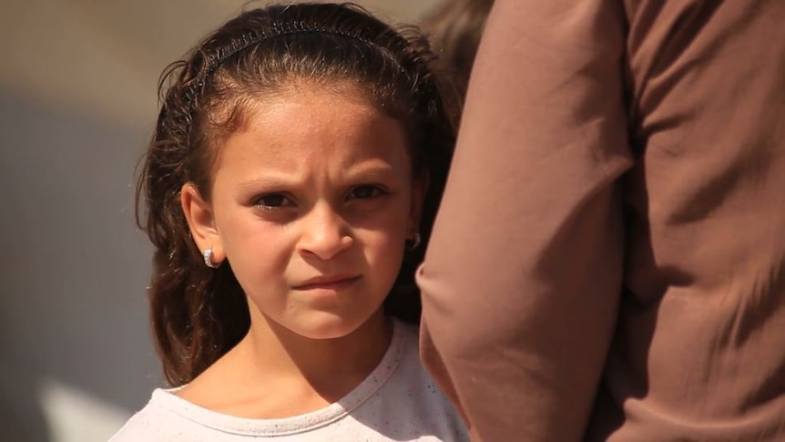 A little girl with a concerned look on her face.