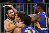 West Coast Eagles players jump all over Josh Kennedy after a match-winning AFL goal against Richmond.