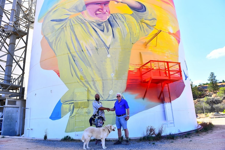 A giant silo painted with a picture of a man looking out across the horizon. There are two men shaking hands and a dog.