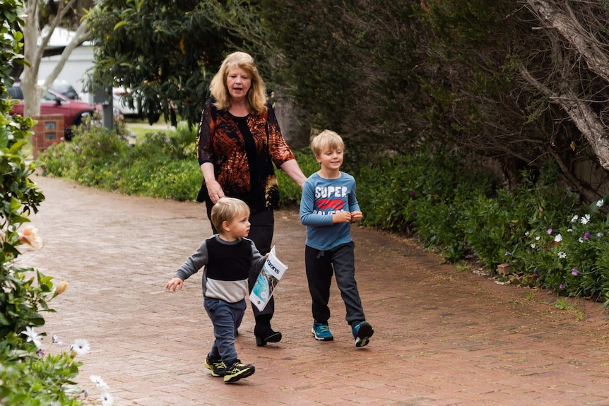Shirley Dix with her grandsons Arlo and Beau walking on the driveway.