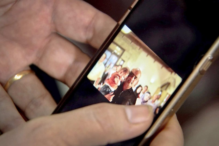 Hands hold a mobile phone featuring a picture of Mohammed Al Halabi.