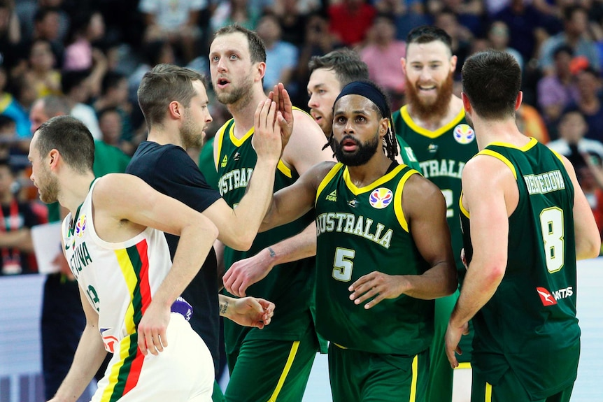 Patty Mills celebrates with boomers teammates, all wearing green singlets with gold trim with Australia in white letters
