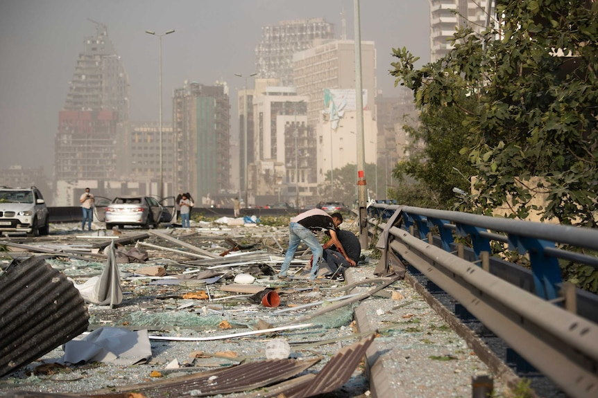 Two men sit amongst broken glass and strewn wreckage on a road with damaged buildings in the background.