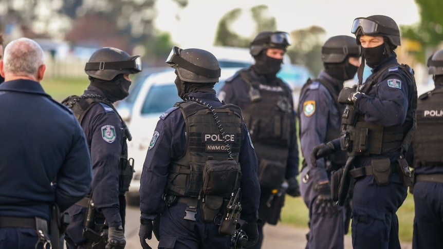 A group of police officers wear helmets, goggles, vests and balaclavas.