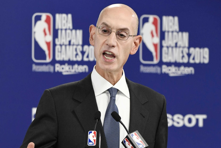 A top basketball executive speaks as he stands in front of microphones at a press conference.