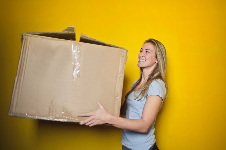 Woman carrying a cardboard box for a story about tips to make moving house easy.
