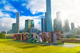 Sunlight streams through Brisbane sign with city building in background at South Bank in CBD