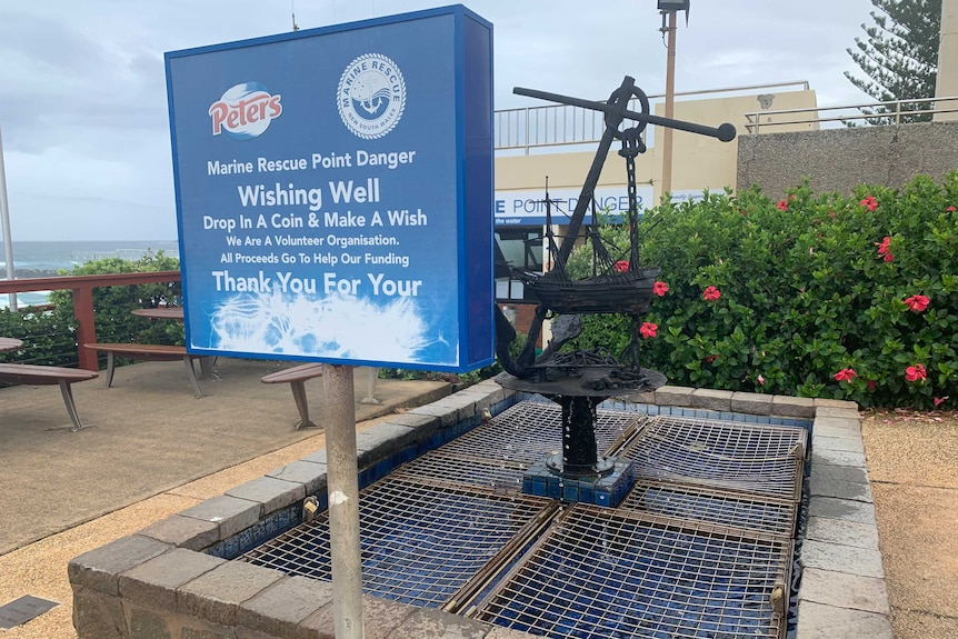 Marine rescue donation sign in front of wishing well featuring an iron anchor and miniature ship sculpture at Point Lookout
