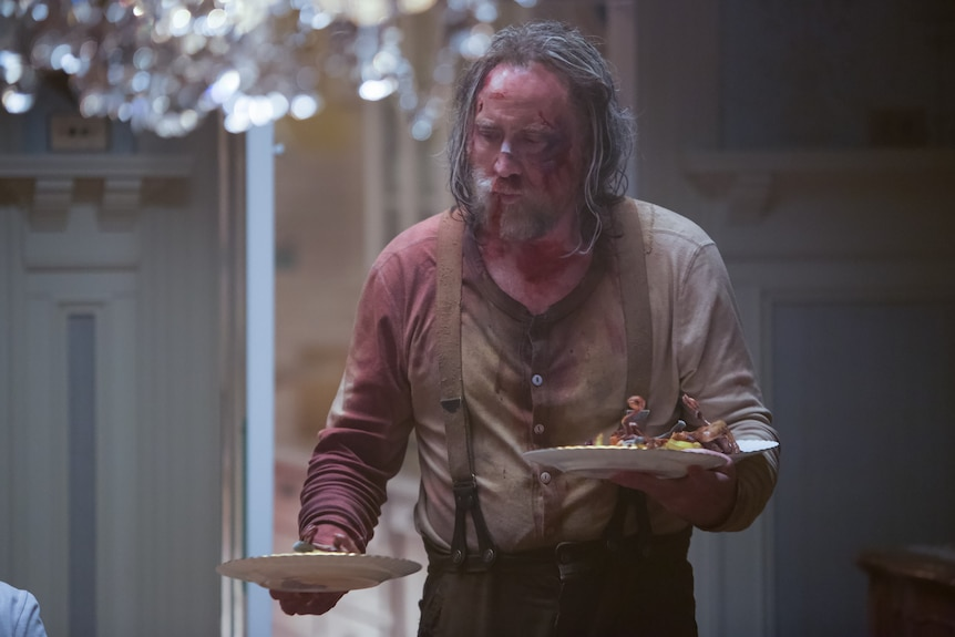 A battered-looking Nicolas Cage with long greying hair and a blood-soaked shirt holds a dinner plate in each hand
