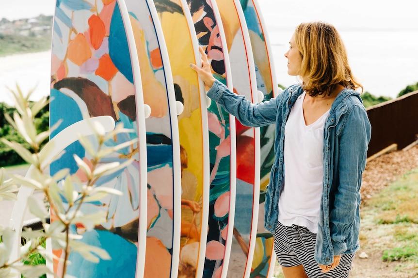 Nusa Indah CEO Jada McNeil with row of colourful surfboards