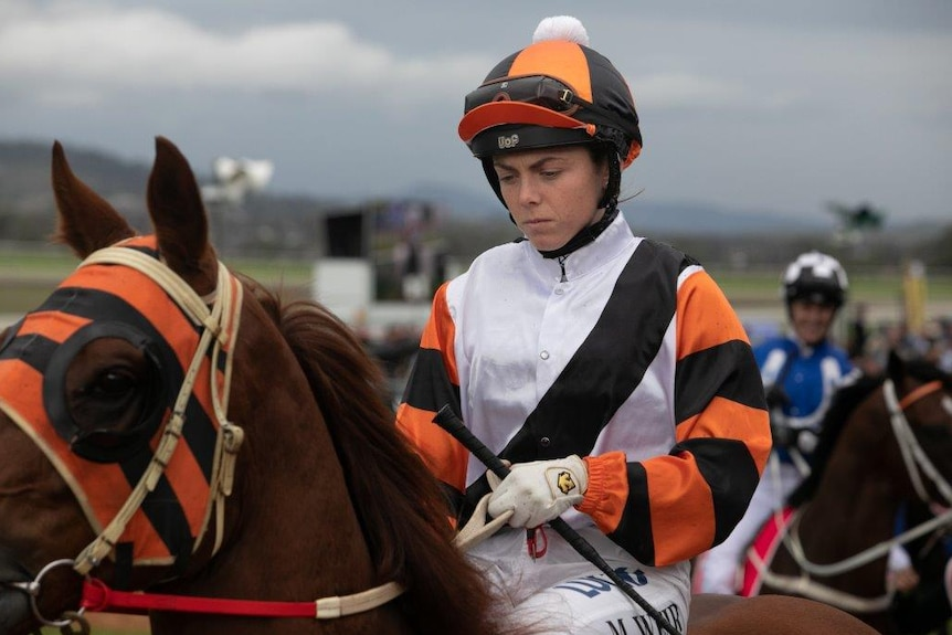 a small woman jockey wearing white black and orange sitting on the back of a race horse after competing.