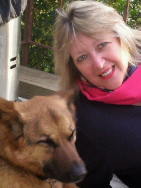 A fair-haired woman is leaning in beside a German shepherd. She is wearing a dark top and a bright pink scarf