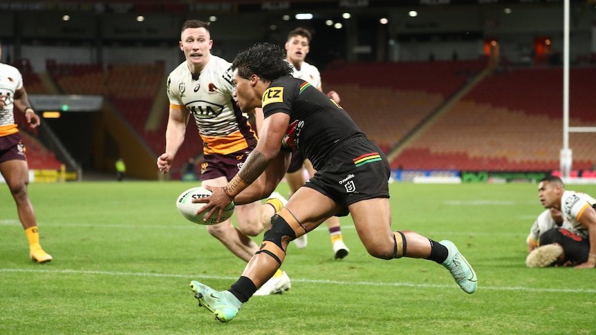 A Polynesian rugby player in a brown jersey scores a try as players in white and yellow look on.
