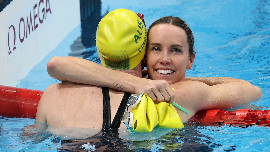 Two Australian swimmers embrace after winning gold and bronze in the women's 100m freestyle.