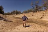 Lower Darling River farmer Rob McBride shows the dry river bed of the Lower Darling River
