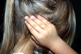 A generic image of a young girl who is unidentifiable, holding her hands to her head.