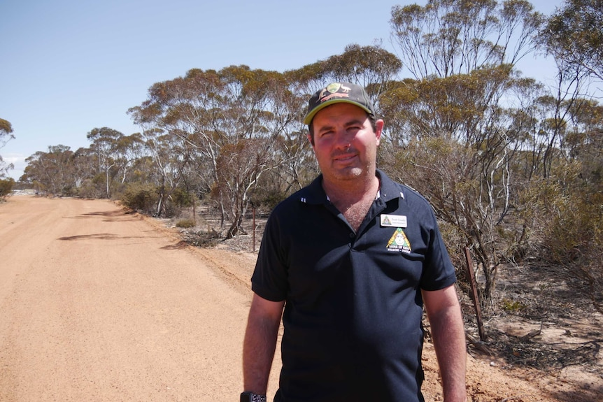A man in a baseball cap and polo shirt stands on a dusty outback road.