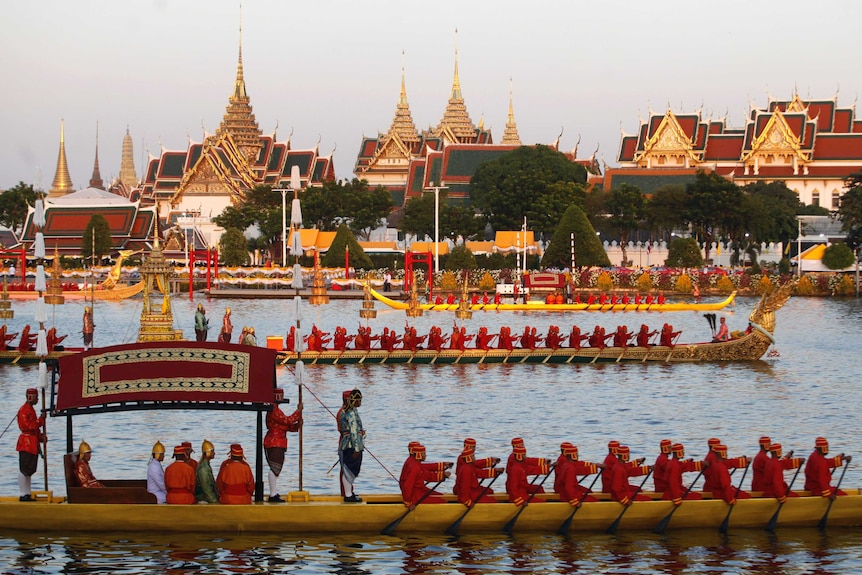 At dusk, you view a series of gold dragon boats on a river directly in front of Bangkok's ornate gold, Grand Palace.
