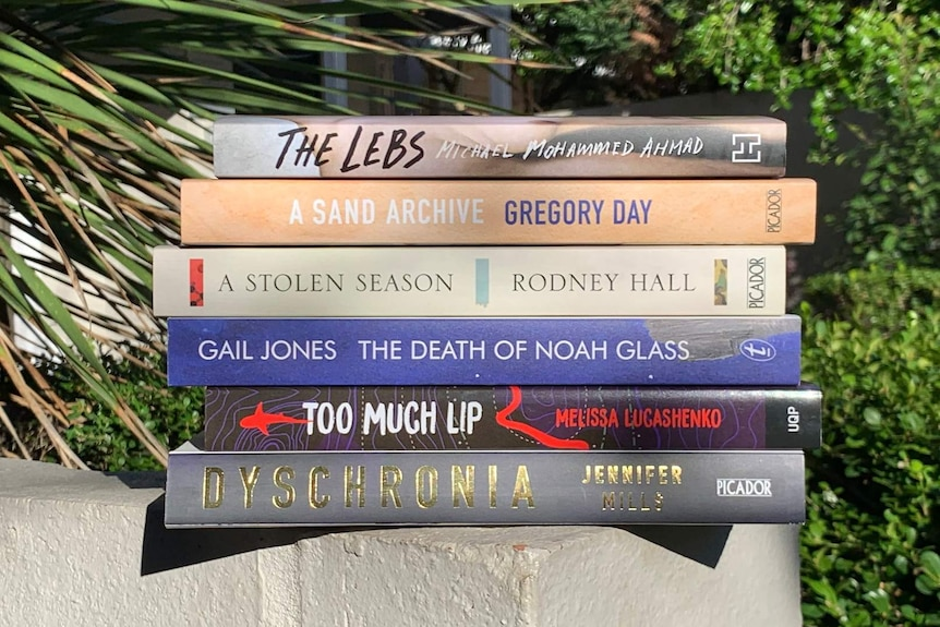 The shortlisted books stacked on a ledge in front of some greenery.