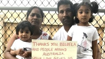 Biloela asylum seeker family, father, mother and two daughters, hold up a sign thanking the community.