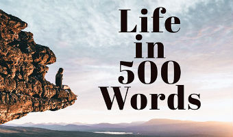 """A person on a rocky out crop looking at a sunrise with words """"Life in 500 Words"""" over the clouds"""