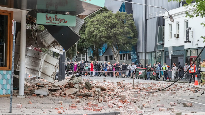 A corner restaurant crumbles to the floor leaving rubble and debris in front of onlookers.