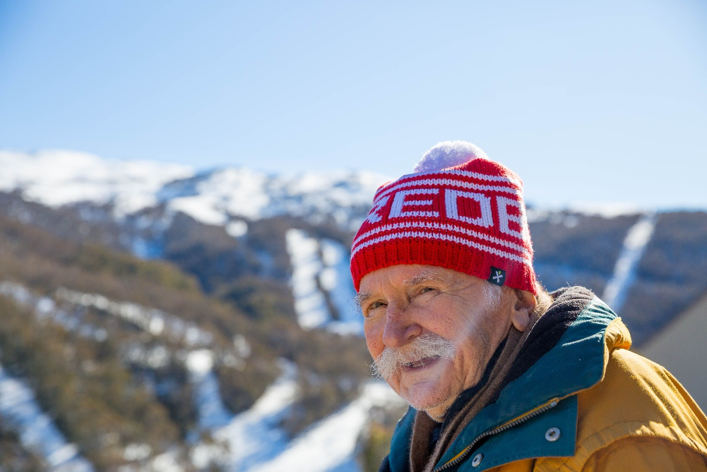 A close up photo of an elderly man wearing a red beanie smiling on a snowy mountain