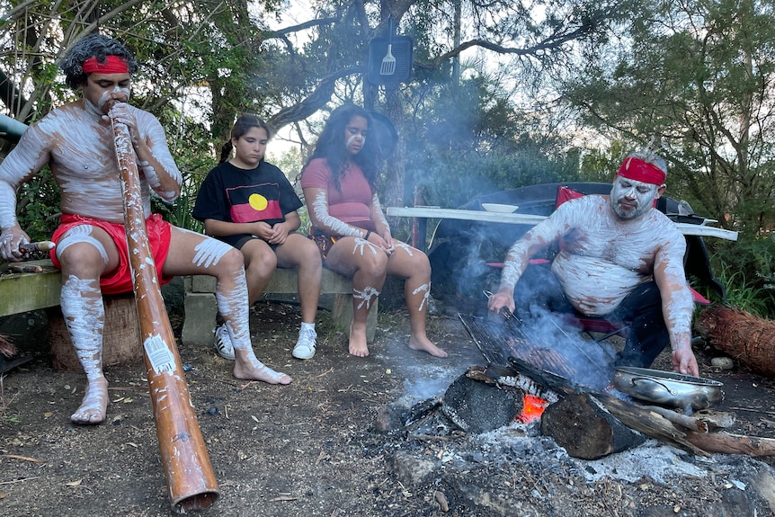 A man in traditional Aboriginal dress cooks over a fire with his two daughters watching. Another man plays a didgeridoo