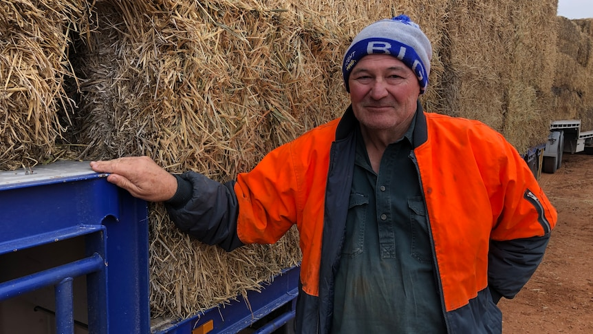 A farmer wearing a beanie and an orange hi-vis vest stands in front of bales of hay that are loaded on a low-loader