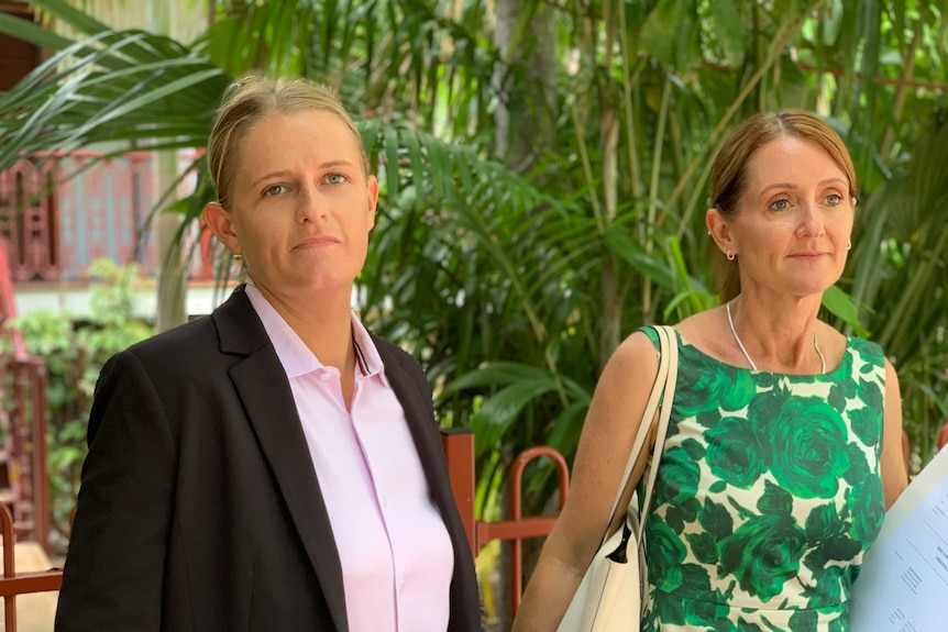 Image of a blonde woman in a pink shirt and black blazer walking next to another woman in a green floral print dress.